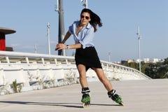 加速在与裙子的右边的女子溜冰者 图库摄影