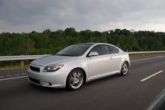 加速在高速公路的银色跑车 免版税图库摄影
