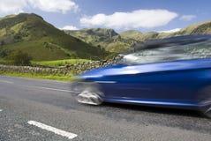 加速英国的蓝色汽车地区湖 免版税库存照片