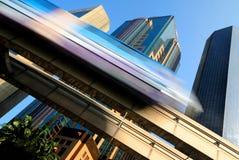 加速通过一个现代商业区的skytrain的行动迷离 免版税库存图片