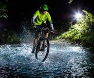 加速通过森林小河的山骑自行车的人 在结冰行动的水飞溅 免版税库存照片