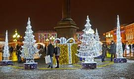 加里宁格勒,俄国 人们在光亮的冷杉木中走在冬天晚上 胜利广场 免版税库存图片