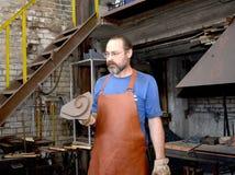 加里宁格勒,俄国 匠拿着手工锻件的一个金属形式 免版税库存照片