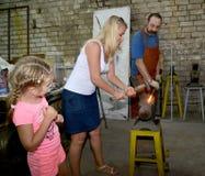 加里宁格勒,俄国 妇女在铁匠铺塑造一个金属制品 免版税图库摄影