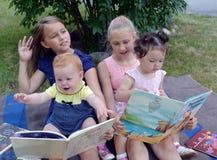 加里宁格勒,俄国 小女孩考虑在书的图片,坐膝部在姐姐 库存图片