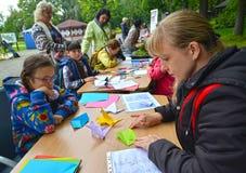 加里宁格勒,俄国 少妇投入origami 儿童` s大师类露天 免版税库存照片