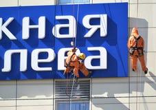 加里宁格勒,俄国 工业登山人通过高压的水槽洗涤一个大厦门面 免版税库存图片