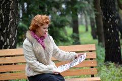 加里宁格勒,俄国 平均岁月的妇女在一条长凳读报纸在公园 免版税库存照片