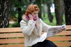 加里宁格勒,俄国 平均岁月的妇女寻找在报纸的工作 免版税库存照片