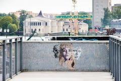 加里宁格勒,俄罗斯- 2015年9月14日:由妇女、人和头骨的未认出的艺术家面孔的街道艺术 免版税图库摄影