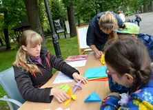加里宁格勒,俄罗斯- 2017年9月17日:老师教学校学生投入origami 儿童` s大师类露天 免版税库存照片