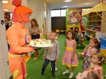 加里宁格勒,俄罗斯- 2016年9月18日:设计卡通者在儿童的生日拿着欢乐蛋糕 免版税库存照片