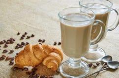 加香料拿铁或咖啡用牛奶在玻璃装饰用油煎的咖啡豆、新月形面包和葡萄酒匙子在棕色布料 库存图片
