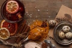 加香料的热葡萄酒、香料和干果子在一张土气桌上 免版税库存照片