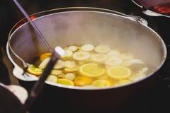 加香料的热葡萄酒用在大大桶的桔子在圣诞节市场上 新年和圣诞节庆祝概念,传统饮料 库存图片