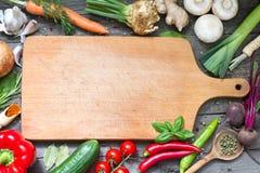 加香料草本和菜食物背景和空的切板 免版税库存照片