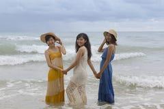 更加年轻的亚裔在海海滩h的妇女朋友松弛假期 库存照片