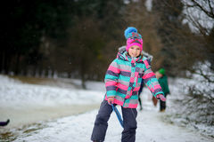 更加年轻的入学年龄的女孩在冬天公园花费时间高兴地 免版税图库摄影