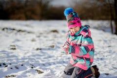 更加年轻的入学年龄的女孩在明亮的滑雪服的做了一个雪球 库存图片
