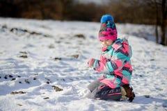 更加年轻的入学年龄的女孩在明亮的滑雪服的做了一个雪球 免版税库存图片