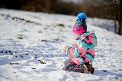 更加年轻的入学年龄的女孩在明亮的滑雪服的做了一个雪球 库存照片