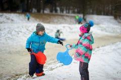 更加年轻的入学年龄的男孩和女孩在冬天停放关于雪橇的倾斜 免版税库存照片