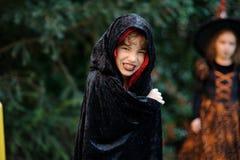 更加年轻的入学年龄的男孩在一个黑红色斗篷的刻画邪恶的巫师 图库摄影