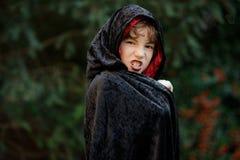 更加年轻的入学年龄的男孩在一个黑红色斗篷的刻画邪恶的巫师 免版税库存图片