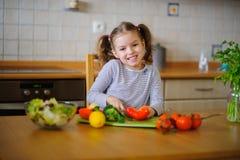 更加年轻的入学年龄的逗人喜爱的女孩削减菜和绿色沙拉的 免版税库存照片