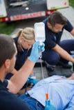 医务人员队滴水为受伤的患者做准备 免版税库存照片