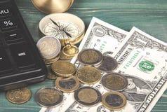 财务的概念 计算器、指南针、欧洲硬币和美金在绿色木桌上 免版税库存照片