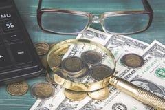 财务的概念 计算器、放大镜、欧洲硬币、英国便士、美金和玻璃在绿色木桌上 免版税库存图片