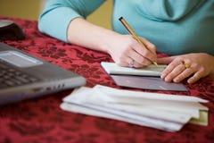 财务:妇女为票据写支票 免版税库存照片