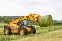移动一个圆的大包的装载者拖拉机从领域 免版税图库摄影