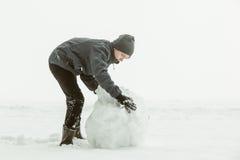 滚动一个大雪球的男孩侧视图 免版税库存图片