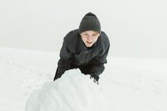 滚动一个大雪球的笑的男孩外面 免版税库存图片