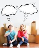 移动一个新的家的年轻夫妇 男人和妇女箱中取出的fragil 免版税图库摄影