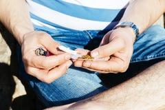滚动一根香烟用辗压烟草的手 免版税库存图片