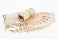 滚动与橡胶的欧元在五十张欧洲钞票扇动 金钱束堆 库存图片