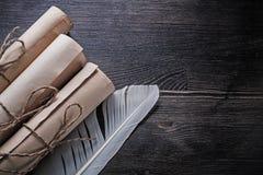 滚动与羽毛的葡萄酒纸在木 免版税库存照片