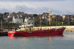 移动向它的停泊处的拖网渔船在一个港口在采取风雨棚的爱尔兰在一场风暴期间在爱尔兰海 免版税库存图片
