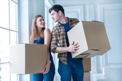 移动向新的生活 拿着移动的女孩和人箱子 免版税图库摄影