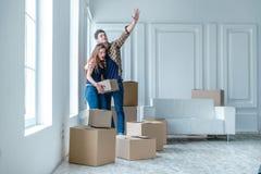 移动向新的生活 拿着移动的女孩和人箱子 免版税库存图片