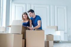 移动向新的生活 拿着移动的女孩和人箱子 免版税库存照片