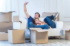 移动向新的生活 拿着移动的女孩和人箱子 图库摄影