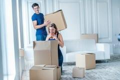 移动向新的生活 拿着移动的女孩和人箱子 库存图片