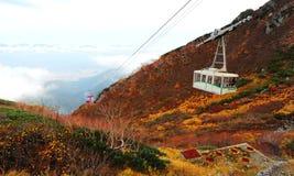滑动在云彩的一辆风景缆车的鸟瞰图由秋天山决定在日本中央阿尔卑斯国家公园, Ngano 免版税图库摄影
