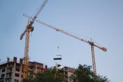 移动在建筑结构下的建筑用起重机 免版税库存图片