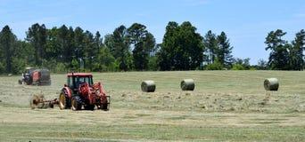 滚动大包干草的拖拉机 图库摄影