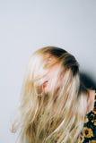 移动她的头发的白肤金发的妇女 库存照片